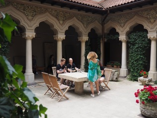 Four drummers exploring the rhythmic capabilities of one stone table in a monastery courtyard